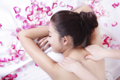 asian woman beauty enjoying shoulder spa treatment with rose flower around