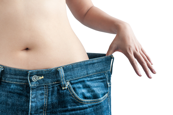 """A Dieting Woman Shows Off An Old Pair Of Jeans, Demonstrating Weight loss"""