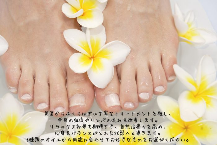 woman's feet soaking in bath surrounded by frangipani flowers